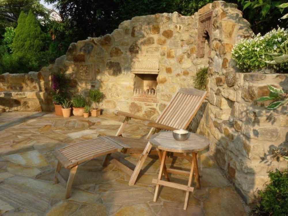 Mediterraner Garten-Sitzplatz mit antik anmutender Natursteinmauer