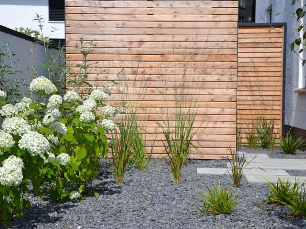 Sichtschutz aus Holz im Kiesbeet
