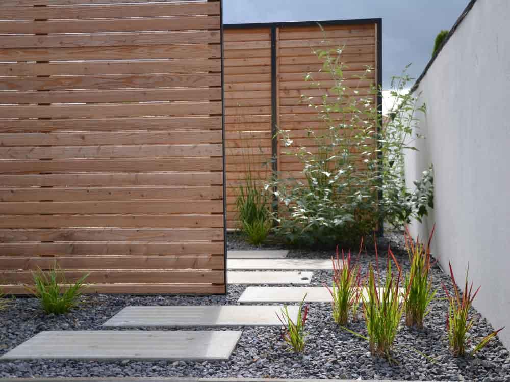 Sichtschutz aus Holz im Kiesbeet und Betonplatten